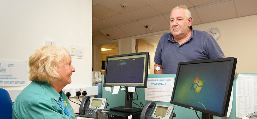 Patient at clinic speaking to receptionist