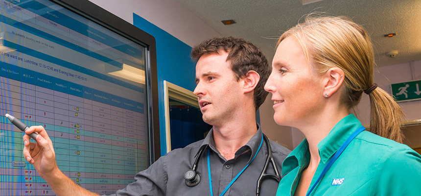 Doctor and Nurse discussing plans detailed on a wall chart